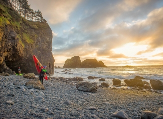 Man with kayak on rocky beach at sunset