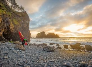 Man with kayak on rocky beach at sunset