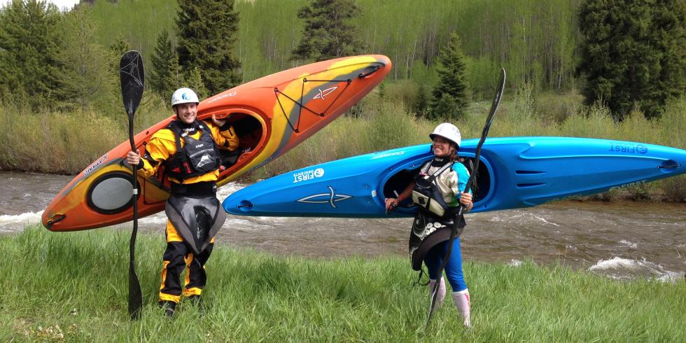 Two Kayakers holding their gear